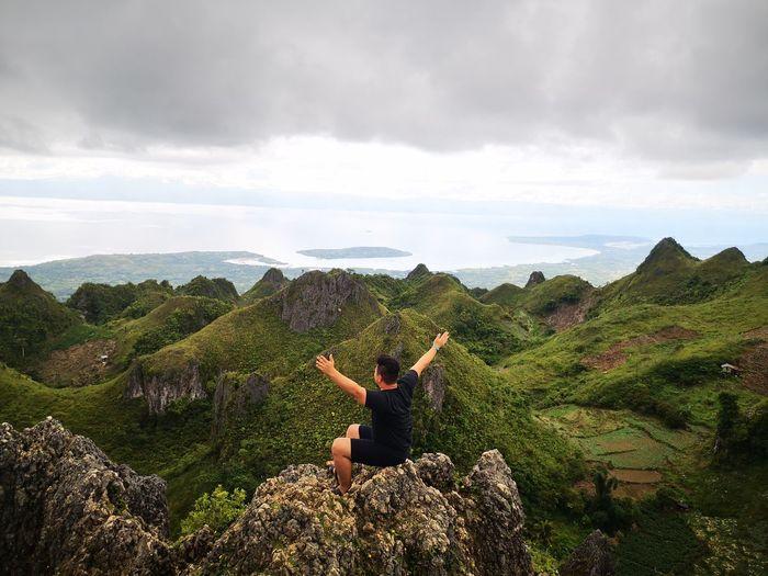 Full length of man sitting on rock against sky