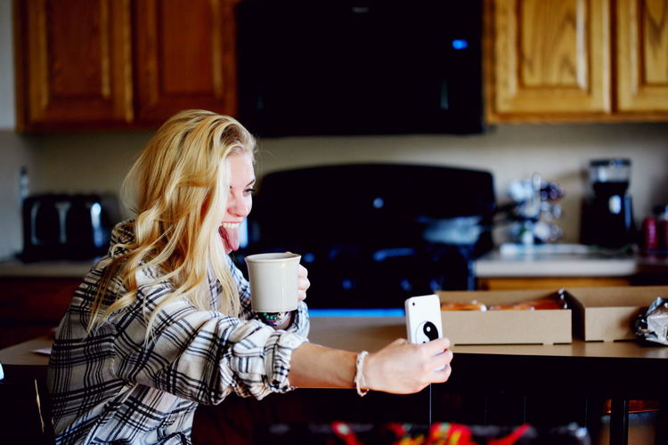 Cheerful Woman Taking Selfie While Drinking Coffee At Home