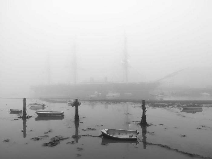 Boats moored in harbor during foggy weather