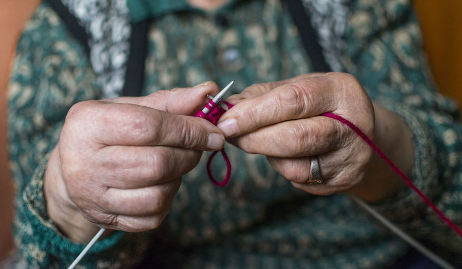 Old woman knitting in home near the window. Human Hand Hand Knitting Needle Knitting Human Body Part Art And Craft Wool Holding One Person Craft Close-up Adult Creativity Midsection Skill  Focus On Foreground Textile Preparation  Women Nail Finger