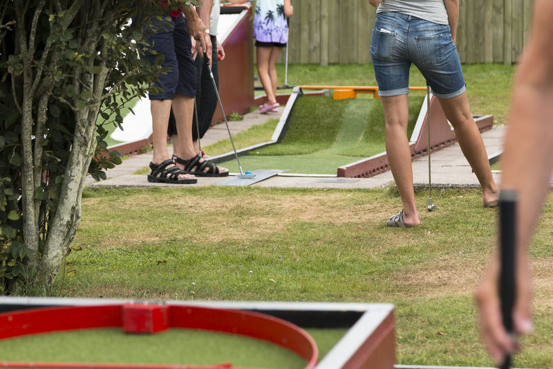 Low section of people playing miniature golf