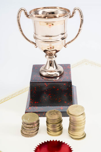 Trophy Cup and coins and blank certificate on white background Indoors  Still Life Studio Shot White Background No People Close-up Stack Metal Success Finance Coin Table Wealth Gold Colored High Angle View Number Cup Reflection Achievement Thread Silver Colored