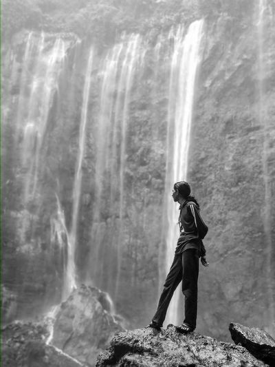 Side view of woman standing on rock against waterfall