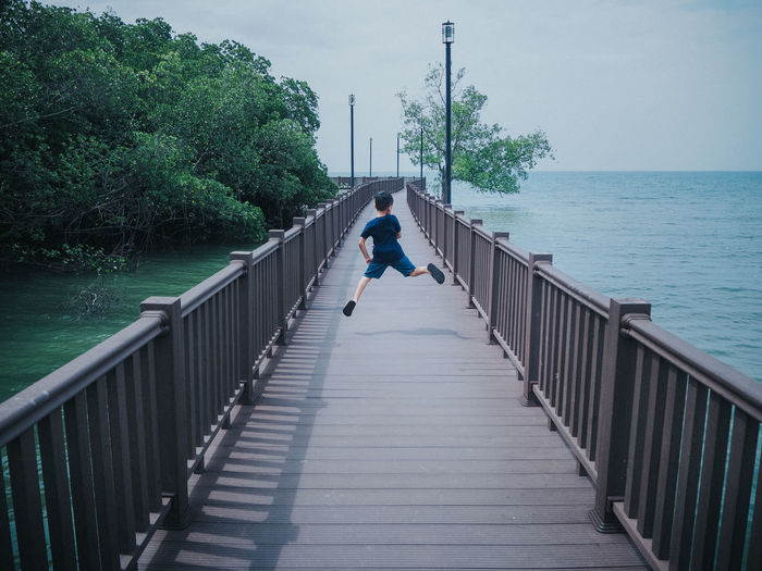 Boy jumping on walkway over sea against sky