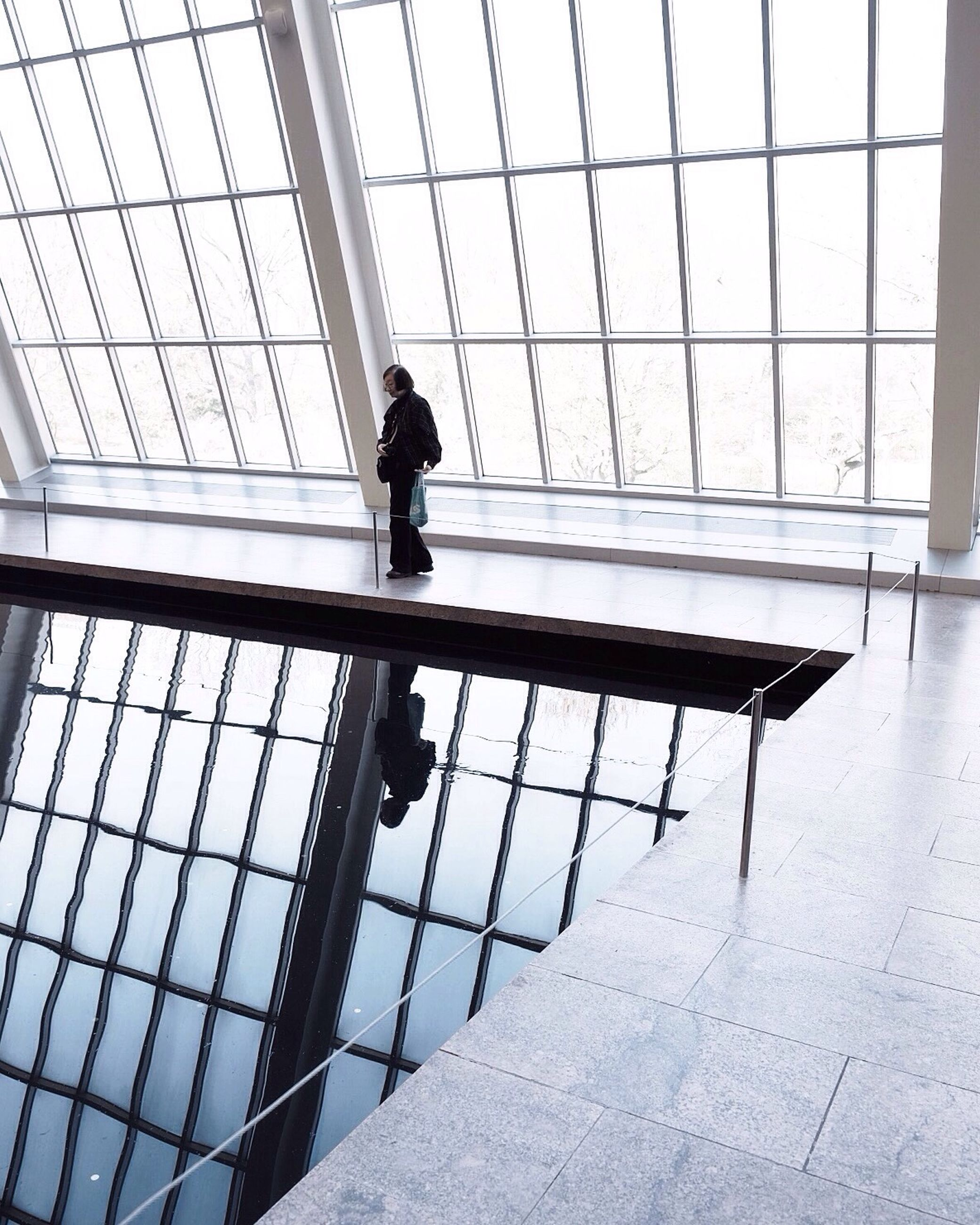 indoors, full length, architecture, built structure, men, lifestyles, glass - material, walking, window, rear view, silhouette, standing, transparent, person, day, tiled floor, railing, leisure activity
