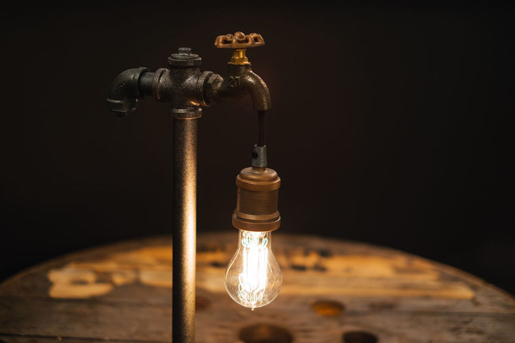Close-up of illuminated electric bulb on tap