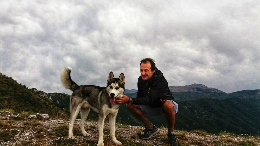 Smiling Mature Man Pampering Dog On Mountain Peak Against Cloudy Sky