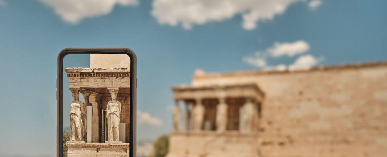 view of ancient Famous statue on smart phone and in the background blurry temple in the area of Acropolis in a sunny day in Greece Athens Group Old Greek Nobody Acropolis Man Landmark Foreigner Outdoors Capital Monument Smart Art Famous Mobile Greece Stone Antique Day Classical Sightseeing Travel Memory View Hands Ruins Building Museum Column Athens Temple History Taking  Tourist Photo Frame Tour Phone People Tourism person Photographer Architecture Ancient
