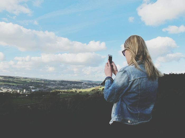 Teenage girl photographing landscape against sky