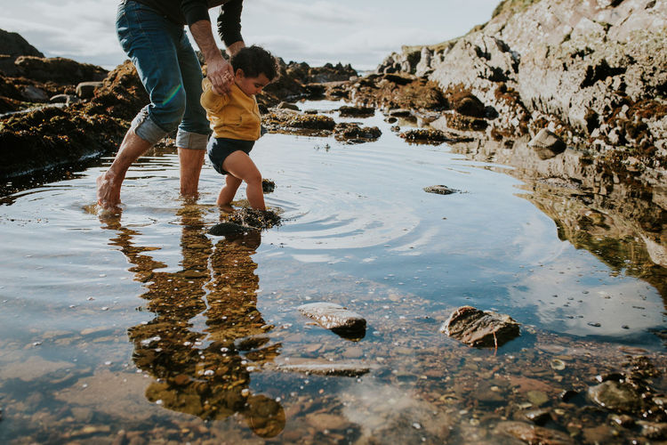 Fatherhood Moments Ankle Deep In Water Casual Clothing Childhood Father And Daughter Girls Leisure Activity Lifestyles Low Section Nature Outdoors People Real People Standing Summer Walking Water Wet