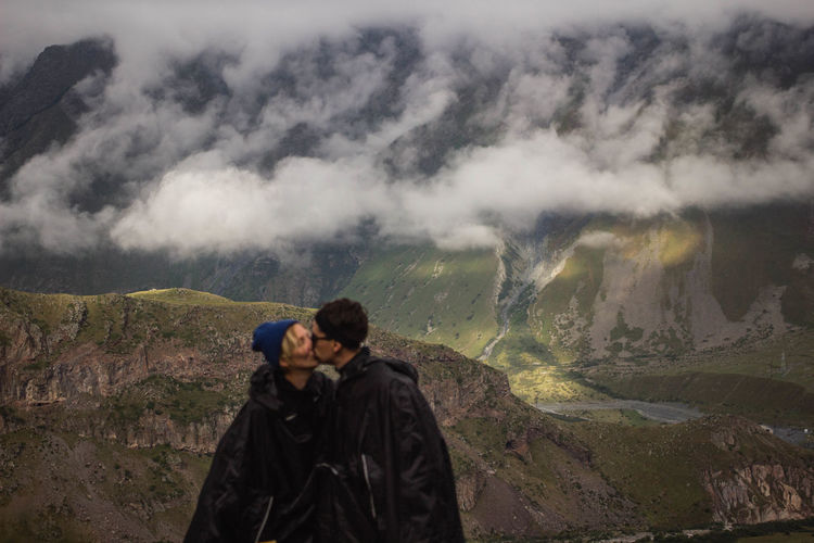 People kissing on mountain against sky during winter