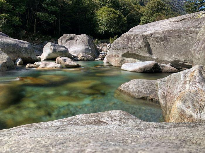 Rocks in river against rock formation