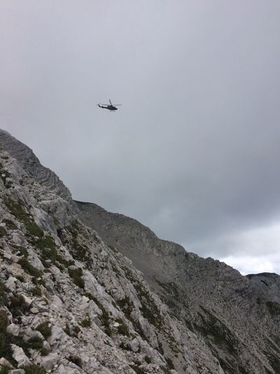 Low Angle View Of Helicopter Flying Over Mountains Against Sky