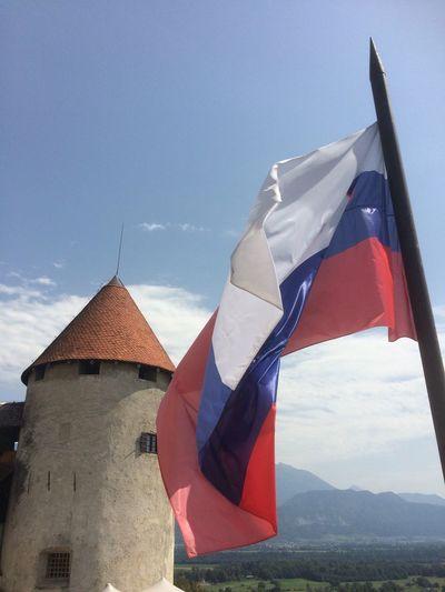 Bled castle and slovakian flag against sky