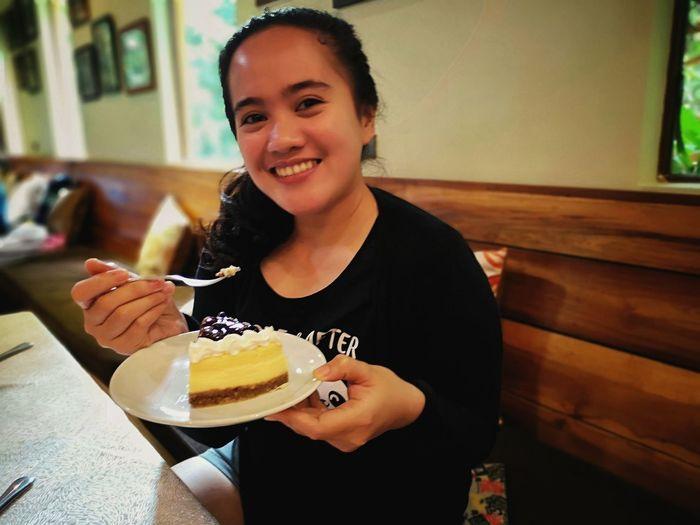 Portrait of smiling woman having dessert in restaurant