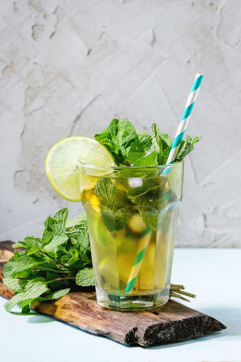 Glass of Iced green tea with lime, lemon, mint and ice cubes on green textile napkin over light blue textured background. Food And Drink Drink Refreshment Food Herb Drinking Glass Mint Leaf - Culinary Glass Leaf Fruit Healthy Eating Freshness No People Cocktail Mojito Lemonade Straw Iced Tea Lime Lemon Sugar Cold Sweet Food Table Light