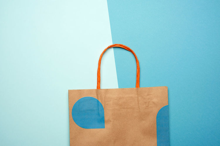 Directly above shot of paper bag over blue background