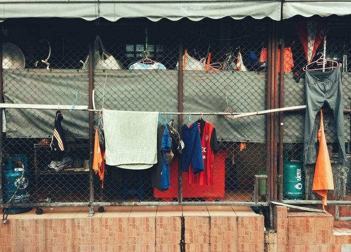 Clothes drying on chainlink fence in back yard