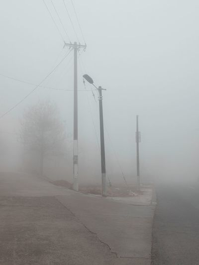 Electricity pylon by road against sky during foggy weather