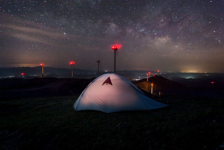 Tent on landscape against sky at night