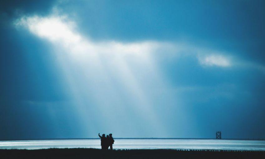 Silhouette people taking selfie at beach against sky