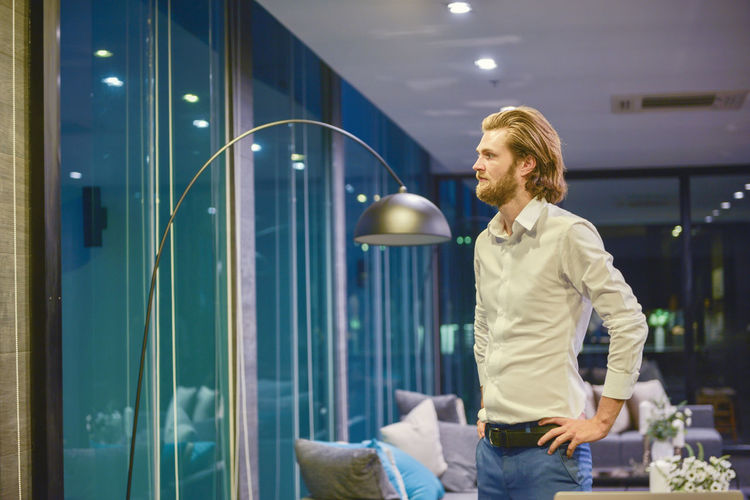Businessman looking through window while standing in office