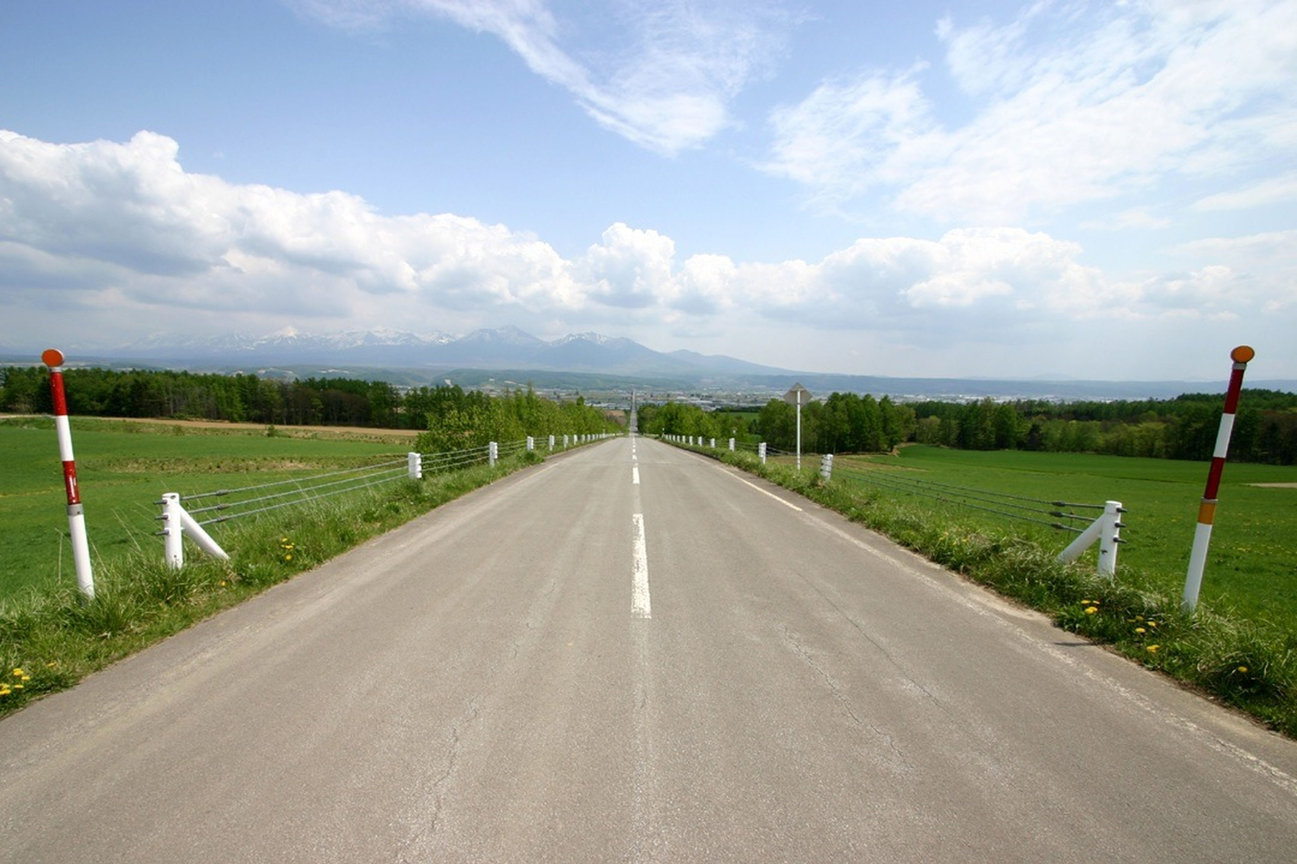 the way forward, road, diminishing perspective, sky, transportation, vanishing point, road marking, country road, landscape, cloud - sky, tranquil scene, tranquility, grass, field, cloud, empty road, empty, nature, cloudy, scenics