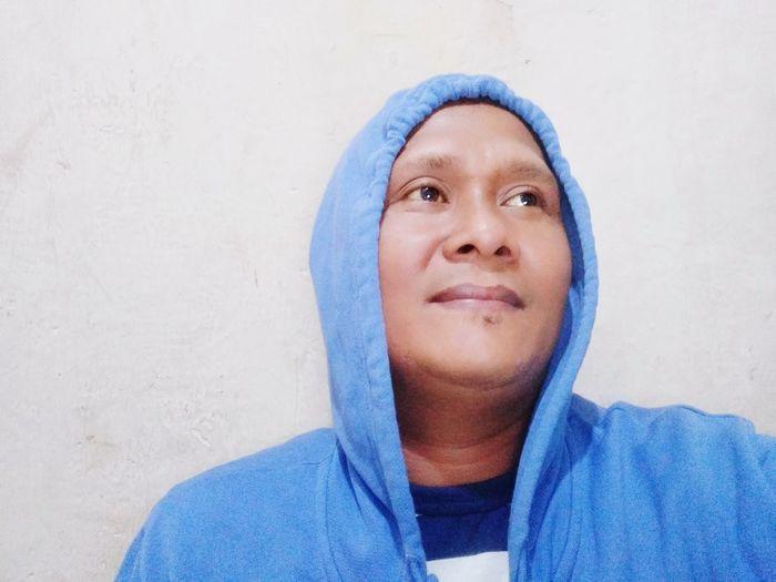 Portrait of man against blue wall