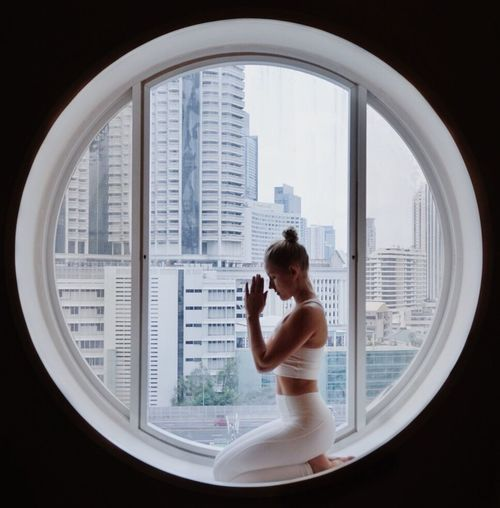 Young Woman Exercising On Window At Home
