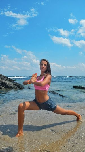 Full length portrait of woman doing yoga at beach against sky