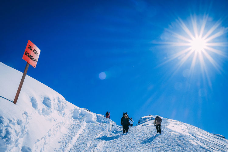 People on snowcapped mountain against blue sky on sunny day