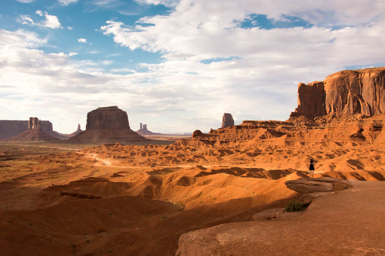 Woman standing on rock formation at monument valley