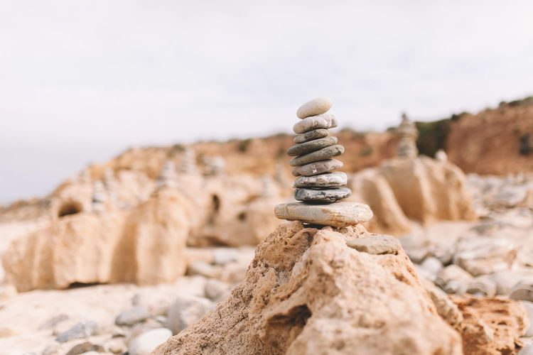 Close-up of stack of pebbles against sky