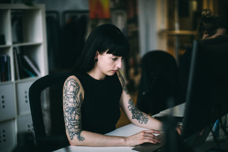 Tattooed Woman Working At Desk In Office