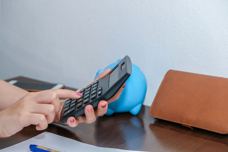 Close-up of person using mobile phone on table
