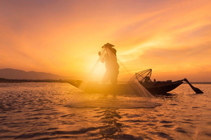 Asian fisherman with wooden boat in nature river during sunrise time,Thailand ASIA Nature Thailand Adult Beauty In Nature Day Fisherman Fishing Holding Lake Landscape Men Nature Net One Person Orange Color Outdoors People River Scenics Sky Sunrise Sunset Transportation Water