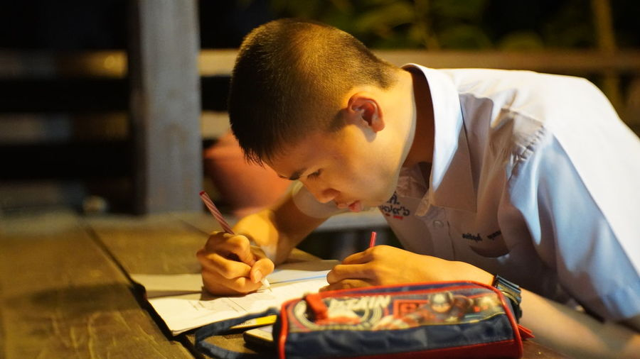 Teenager boy writing on table