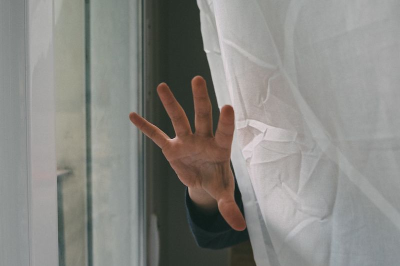 Close-up of human hand against curtain