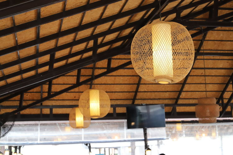 Low angle view of illuminated pendant light hanging from ceiling