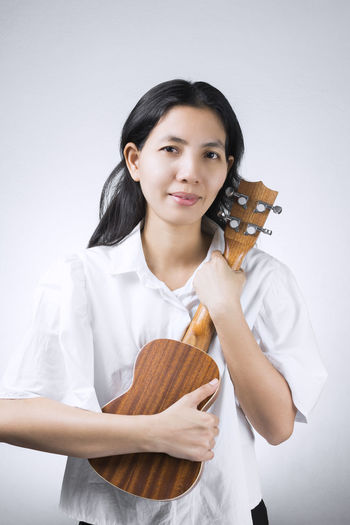 portraits Female Musician who embraces his favorite musical instruments cherish on white background. Asian Woman Thailand Beautiful Woman Casual Clothing Front View Hairstyle Holding Indoors  Looking At Camera Musical Instrument One Person Portrait Skill  Smiling Standing String Instrument Studio Shot Three Quarter Length Ukulele Waist Up White Background Women Young Adult Young Women