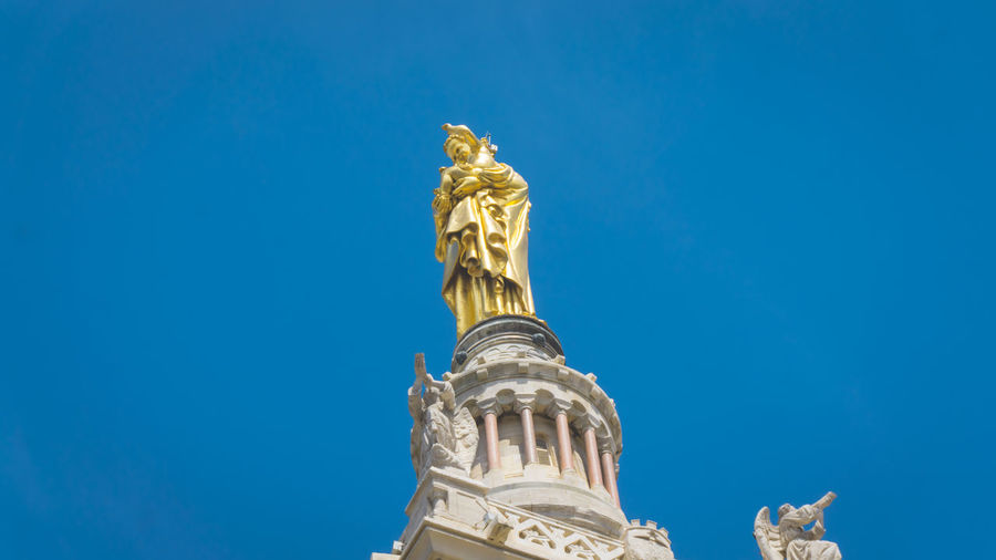 Low angle view of statue of temple against blue sky