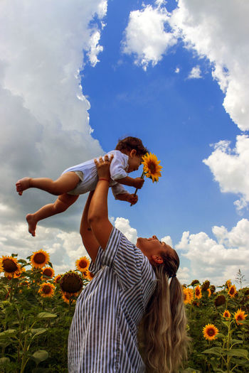 Mother holding boy with sunflower at field against sky