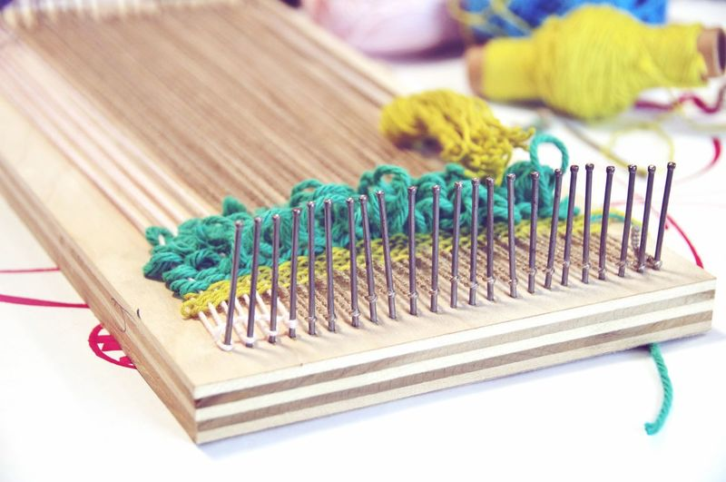 Close-Up Of Needles And Wool On Wooden Plank At Table