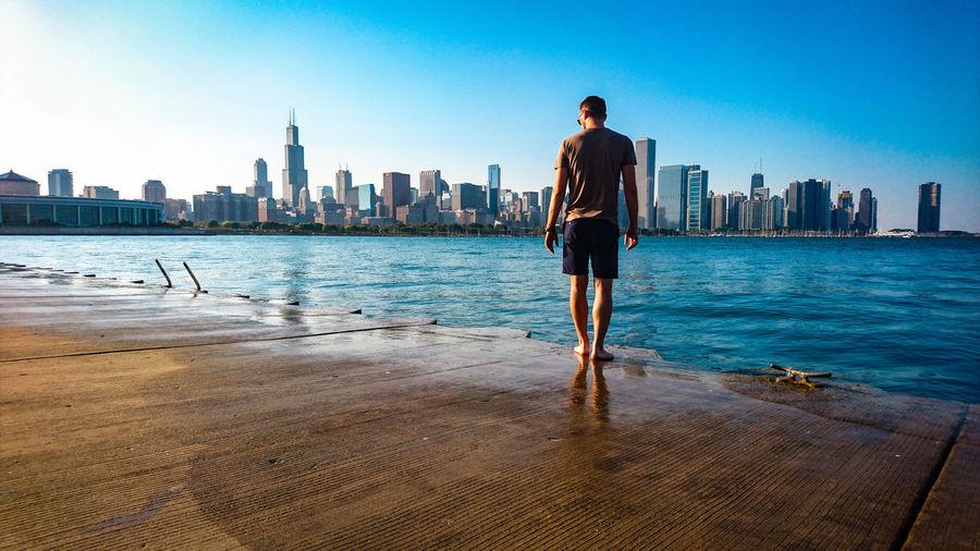 Full length of man standing on promenade against blue sky in city