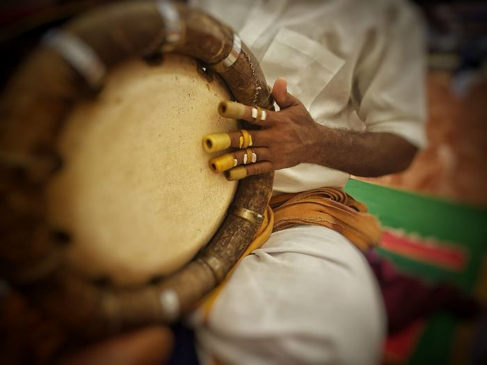 Midsection of man playing tabla during traditional ceremony