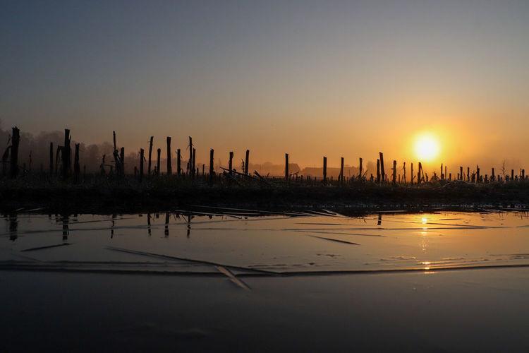 Silhouette wooden posts in lake against orange sky