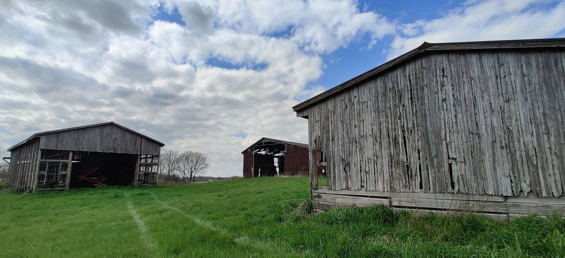 Panoramic shot of abandoned house on field against sky