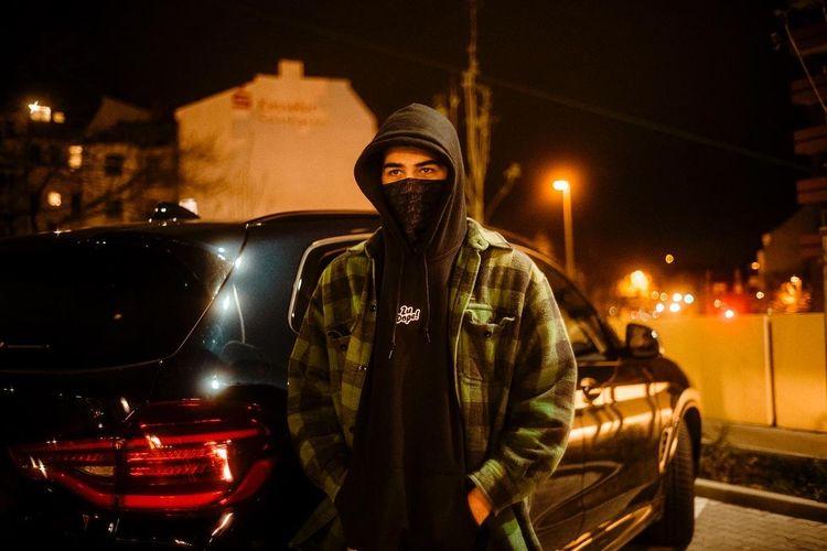 Portrait of man standing on illuminated street at night