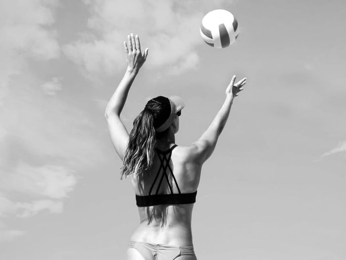 Midsection of woman with ball in background against sky