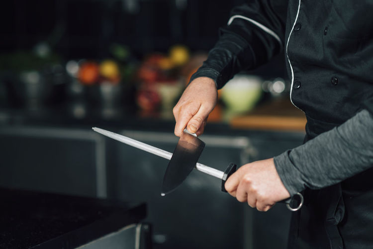 Midsection of chef sharpening knife